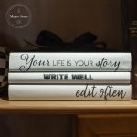 White books painted with black lettering: Your life is your story, write well, edit often
