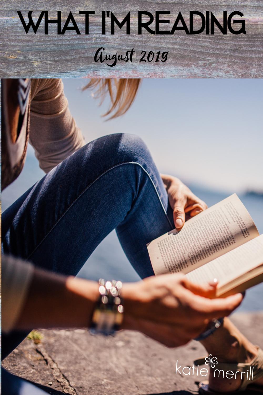 woman readinng book next to a lake